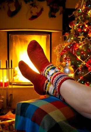 ohniště: dívka odpočívá v domě s hořícím krbem a vánoční strom Reklamní fotografie