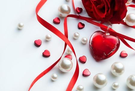 perlas: el arte de San Valentín tarjeta de felicitación con pétalos de rosas rojas y el corazón de joyas en el fondo blanco Foto de archivo