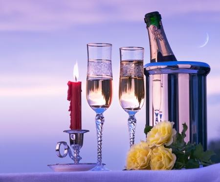 cena romantica: felice cena romantica con il vino sullo sfondo del cielo