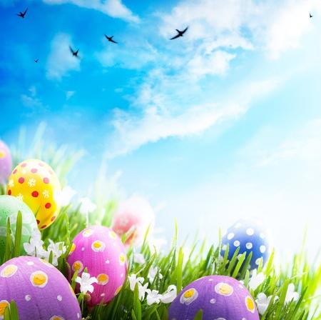 osterei: Bunte Ostereier mit Blumen im Gras auf Hintergrund des blauen Himmels geschmückt