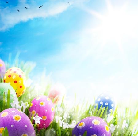 Kleurrijke paaseieren versierd met bloemen in het gras op blauwe hemel achtergrond
