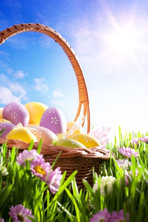 art Easter basket with Easter eggs on spring lawn Stock Photo