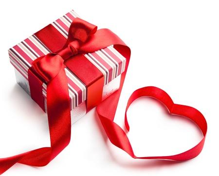 aniversario: caja de regalo de Navidad con la cinta roja en la forma de un coraz�n aislado en el fondo blanco Foto de archivo