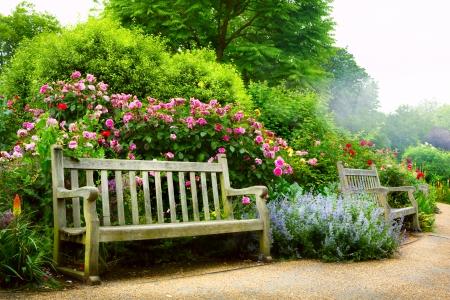 Art bank en bloemen in de ochtend in een Engels park Stockfoto