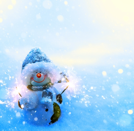 Art Christmas snowman and sparklers on blue snow background photo
