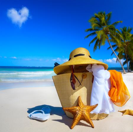 sunglasses: Sombrero de paja de arte, bolso, gafas de sol y sandalias en una playa tropical