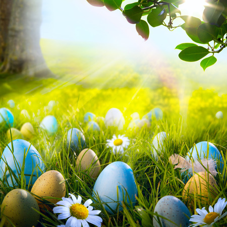 Art decorated easter eggs in the grass with daisies photo