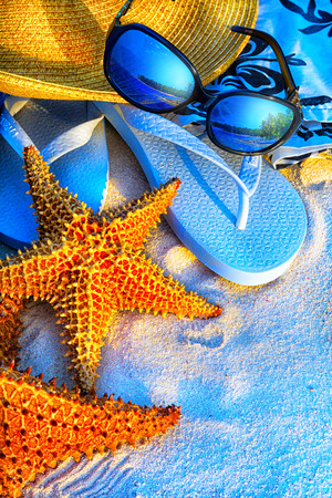 Art Summer holidays sea beach  background. Pair of flip- flops in the sand with starfish  photo