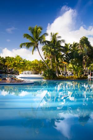 tropisch: Kunstliegestühle in tropischen Resort Hotel-Pool Lizenzfreie Bilder