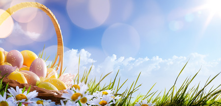 canestro basket: Colorate uova di Pasqua decorate con fiori in erba su sfondo blu cielo Archivio Fotografico