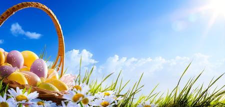 feld: Bunte Ostereier mit Blumen im Gras auf Hintergrund des blauen Himmels geschmückt