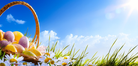 Colorful Easter eggs decorated with flowers in the grass on blue sky background