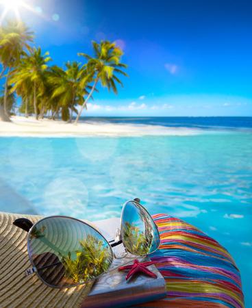 熱帯のビーチに麦わら帽子、バッグ、太陽メガネ 写真素材