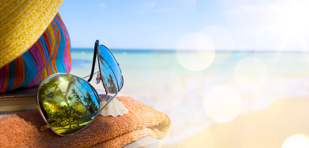 Straw hat, bag and sun glasses  on a tropical beach photo