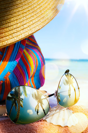 Chapéu de palha, bolsa e óculos de sol em uma praia tropical Imagens