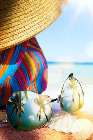 vacaciones en la playa: Sombrero, bolso y gafas de sol de la paja en una playa tropical