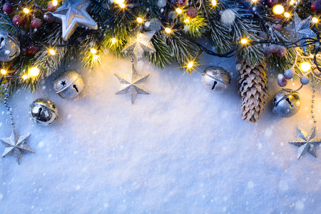 christmas decorations: Christmas background with a silver ornament, christmas stars, berries and fir in snow Stock Photo