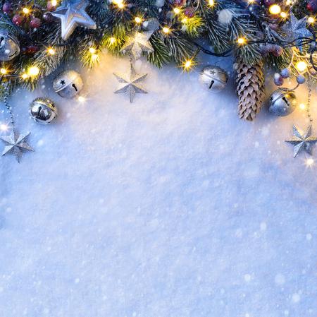 Fondo de Navidad con un adorno de plata, estrellas de la navidad, bayas y el abeto en la nieve