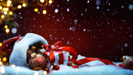 Christmas tree light; festive background with Christmas balls and gift box on snow Foto de archivo