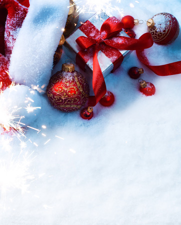 light background: Christmas background with a red ornament, gift box in snow