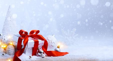 Kerst boom licht; feestelijke achtergrond met kerstballen en gift box op sneeuw