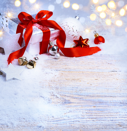 Christmas tree light; festive background with Christmas balls and gift box on snow Banque d'images