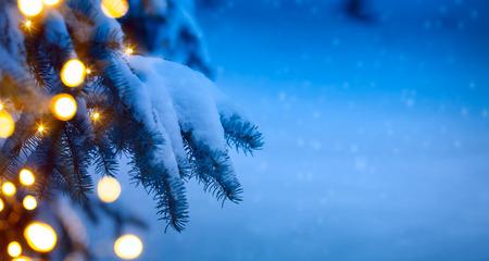 krajobraz: choinki światła; niebieskim tle śniegu
