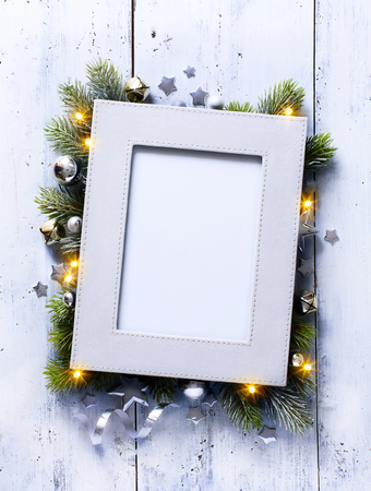 retro frame: Christmas background with fir branches and frame on the old wooden board in vintage style