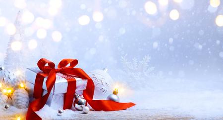 christmas gift box: Christmas tree light; festive background with Christmas balls and gift box on snow Stock Photo