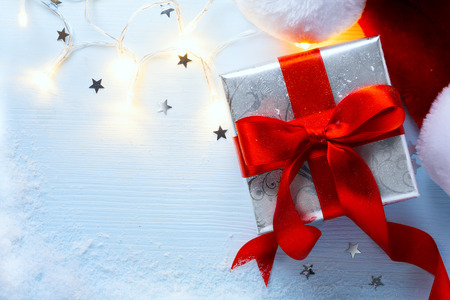 christmas gift box: Christmas  festive background with  gift box and hat of Santa Claus