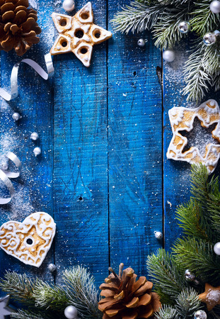 Christmas blue wooden background with snow fir tree and Christmas cookies Banco de Imagens - 49742949