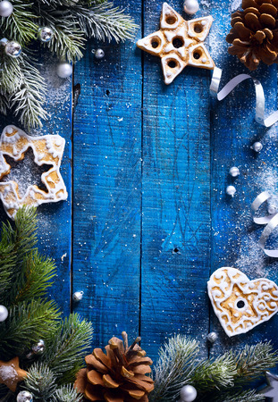 Christmas blue wooden background with snow fir tree and Christmas cookies