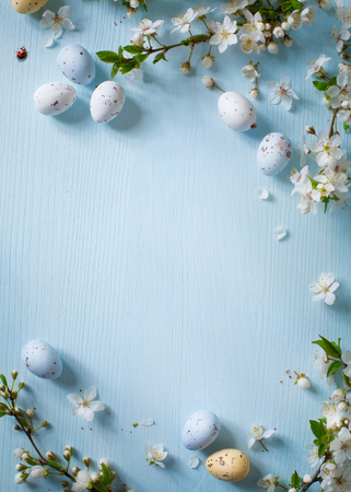 Easter eggs and spring flowers on wooden background Stock Photo