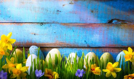 Pasen achtergrond met paaseieren en de lente bloemen op groen gras