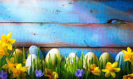 background: Antecedentes de Pascua con los huevos y flores de primavera en la hierba verde