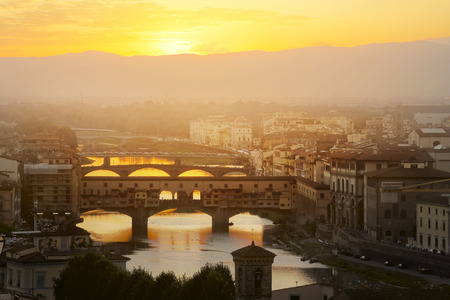 ponte: Evening over the Florence. Arno river and famous Ponte Vecchio enlighten by the warm sunlight. Italy.