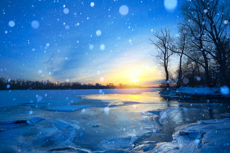 winter landscape panorama; sunset on the bank of a frozen river; ice and snow