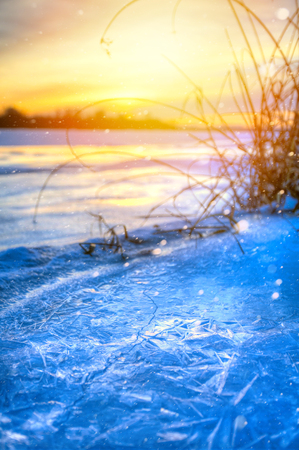 winter landscape panorama; sunset on the bank of a frozen river; ice and snow  Stock Photo