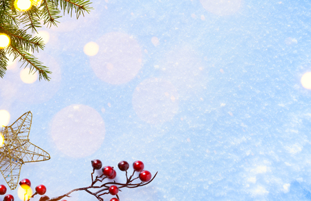 composition: Christmas background with Christmas ornament; holly berry and holiday light on blue snow