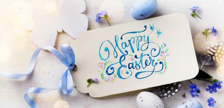 De kaart van Pasen; Paaseieren en de lente flovers op hout achtergrond Stockfoto
