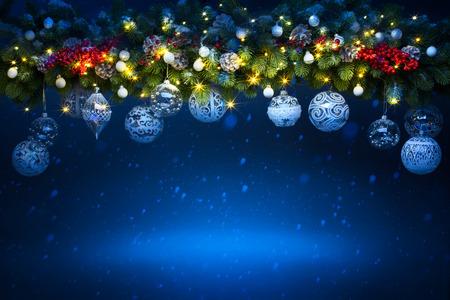 아트 크리스마스 휴일 장식; 전나무 나뭇 가지와 푸른 빛나는 배경에 휴가 빛