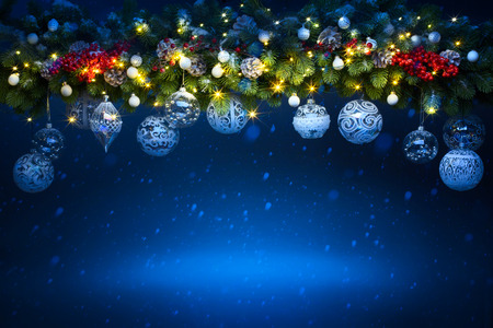 Art Christmas holiday decoration; Fir tree Branches and holiday light on blue snowy background