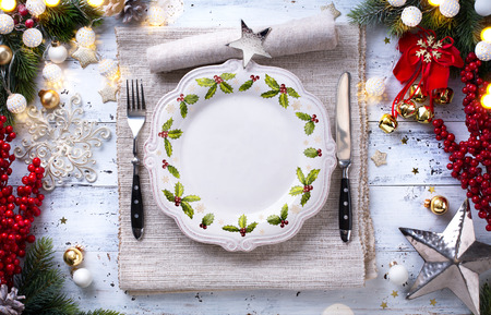 Christmas holiday dinner background; empty dish, cutlery and Christmas tree decoration  Stock Photo