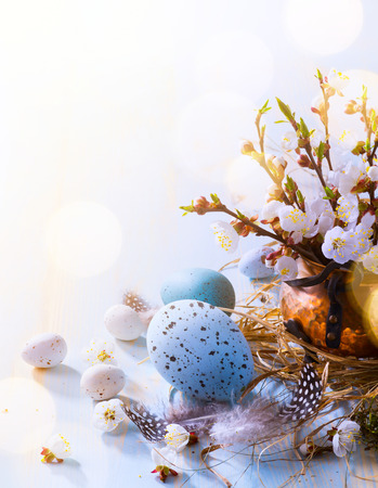Happy Easter;  Easter eggs and sprig flowers on blue table background   Stock Photo