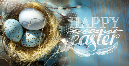 Happy Easter; Easter eggs  in basket on the blue table  background   Stock Photo