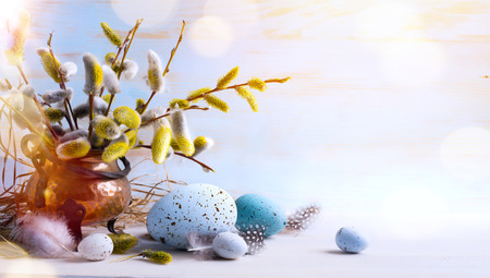 Happy Easter greeting card;  Easter eggs and sprig flowers on blue table background   Stock Photo