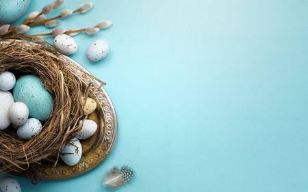 Easter background with Easter eggs and spring flowers on blue table