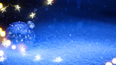 Christmas tree  light and holidays decoration on blue snow background