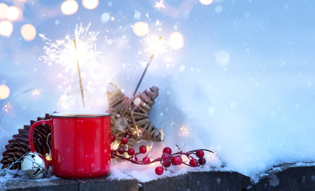 Winter hot drink and Christmas holidays light on snow.