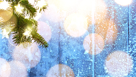Merry Christmas – blue snowy   and fir tree branches with holidays lights